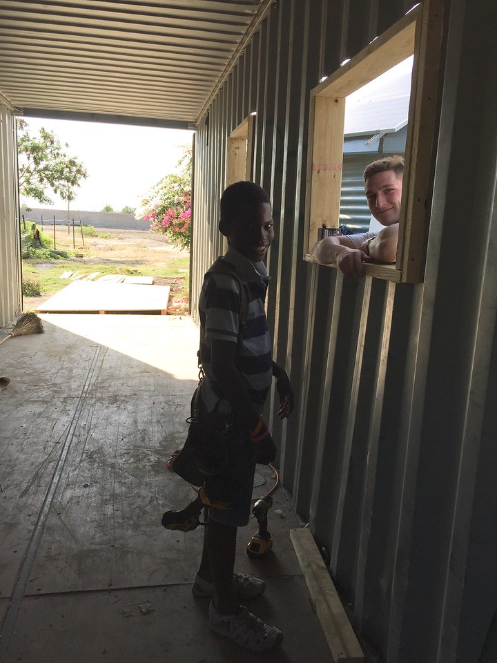 DAY 3<br /> We had to make wooden frames to hold the door & windows. We made them out of treated 2x6's & 2x4's then then bolted them in place to the container. These gave us a nice clean opening that we could control the size of and make sure that it was square.<br /> Here, Richard & Dustin are testing out the walk-up window to order rice & beans...<br /> Richard was a BIG help on my last conex box conversion and I was looking forward to having him as a helper this year. Because the kids were still in school this trip, he wasn't able to help out as much.
