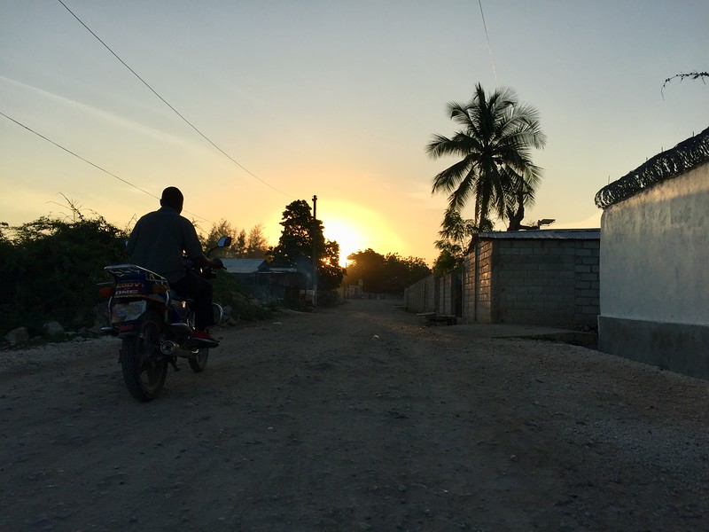 DAY 10<br /> Sunrise on the street in front of the team house as a moto taxi passes by