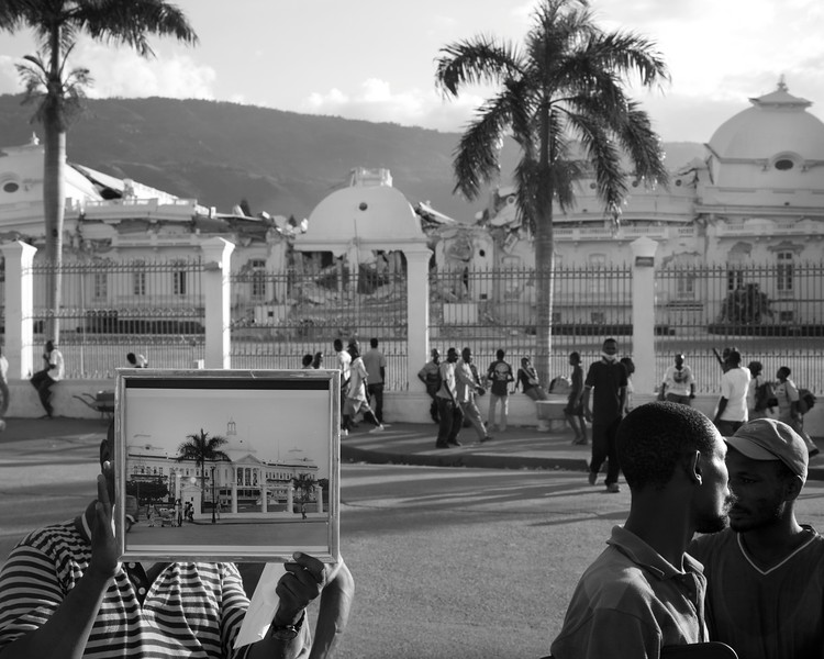 Man shows off the former glory of the Presidential Palace against the current reality.