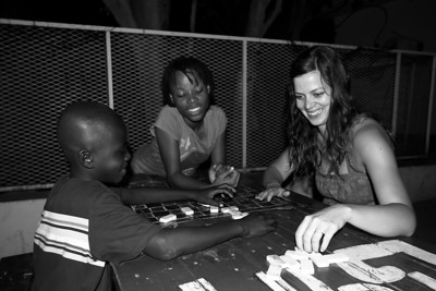 Michelle playing dominoes with Keso who is cheating while Erta looks on.