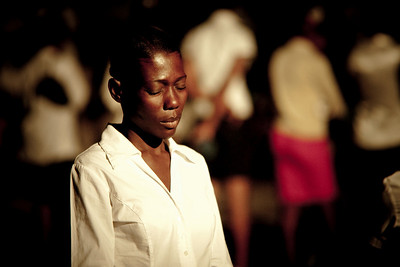 Local church volunteer prays during the crusade. Carrefour, Haiti