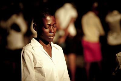 Local church volunteer prays during the crusade. Carrefour, Haiti