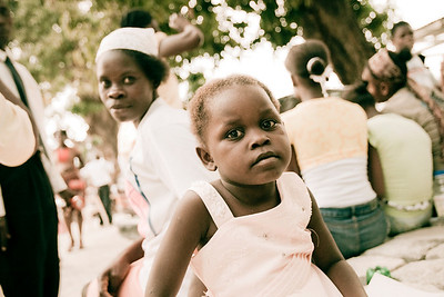 A young girl poses while her mother looks on. Carrefour, Haiti