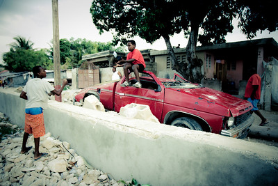 Kids playing on a crushed vehicle in Carrefour, Haiti