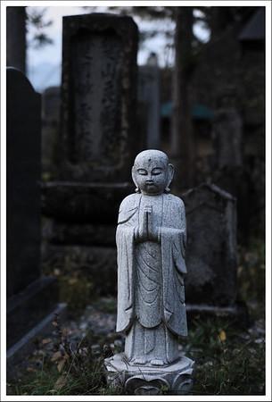 A little Buddha guarding a cemetery just before dark.