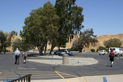 The empty parking lot. This stuff is cool! And nifty! Why don't more people stop?  Oh, right--they're on their way to a dog agility event. Linda (right) roams back to our van (in the shade behind the white car; did I mention that it's hot?).   Next -- on to the national memorial cemetery: https://elf1.smugmug.com/Travel/Havasu-Falls-Grand-Canyon-May/Day-1B-San-Joaquin-Valley/i-hqm9Xf7/A