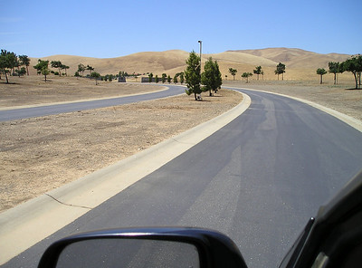 """But the road continues past the """"END"""" sign, so we drive cautiously along the gently curving lane.  We begin passing evergreens planted in the median, each with a small plaque."""