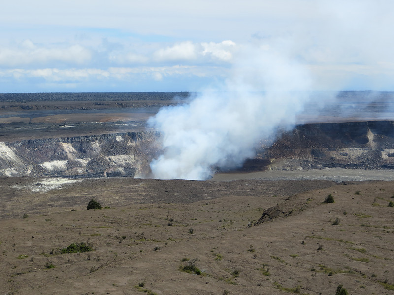 """We learned a new word: """"vog.""""  It is a mixture of water vapor, carbon dioxide, and sulphur dioxide.  (My guidebook says Kilauea emits 2,500 tons of sulphur dioxide every day.)  The gases react with sunlight, oxygen, dust particles, etc. to form a variety of unpleasant compounds.  The tradewinds blow toward the southwest and carry the vog down the coast, around Mauna Loa at the bottom, and up the coast to Kona.  It can really bother people, apparently, but I wasn't aware of it while we were there."""