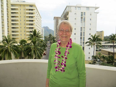 """On the balcony of our hotel room.  When we booked, we asked for a """"city view"""" room (cheaper than ocean view) because we thought we'd get plenty of opportunity to see the ocean on the cruise.  However, our room had a nice view of its own.  I think that is Diamond Head in the background.  I am still in the dazed, """"I can't believe I'm in Hawai'i"""" look."""