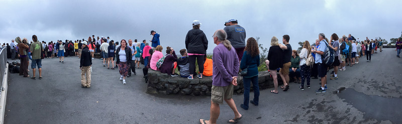 "iPhone pano of shoulder-to-shoulder tourists gathering along the viewing wall at the Jaggar Museum Overlook to see the evening ""Lava Glow"" at Volcanoes National Park, The Big Island, HI - March 2018"