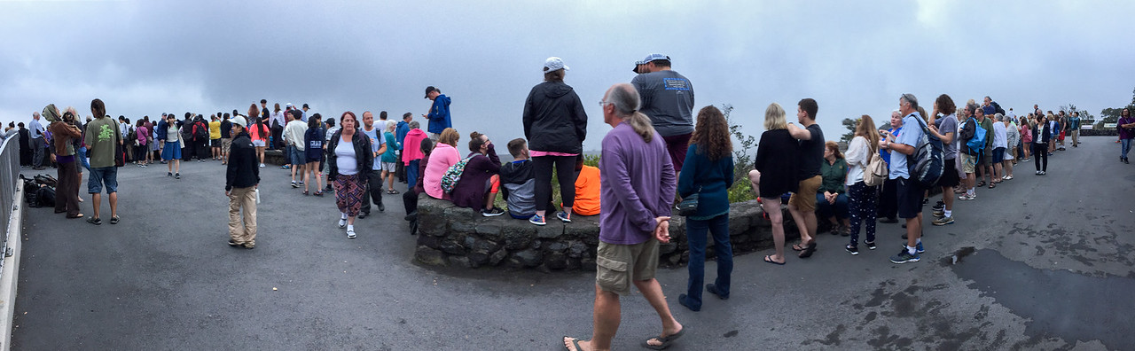 """iPhone pano of shoulder-to-shoulder tourists gathering along the viewing wall at the Jaggar Museum Overlook to see the evening """"Lava Glow"""" at Volcanoes National Park, The Big Island, HI - March 2018"""