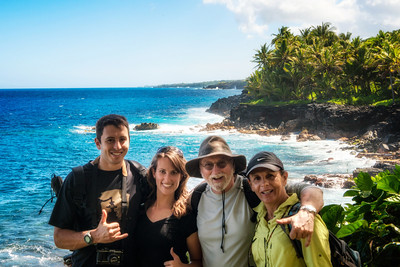 The four happy travelers, overlooking a black sand beach on the south side of the big island.