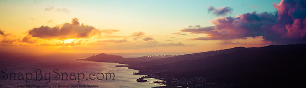 A panorama of a sunset over the Hawaiian Island of Oahu as seen from a mountain top with the city of Waikiki Beach and Diamond Head in the distance.