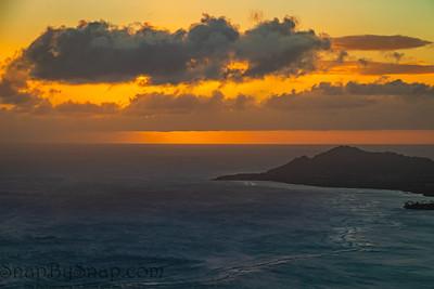 A sunset over the Hawaiian Island of Oahu as seen from a mountain top with Head in the distance.