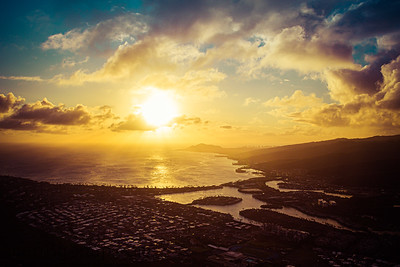 A sunset over the Hawaiian Island of Oahu as seen from a mountain top with the city of Hawaii Kia in the foreground and Diamond Head in the distance.