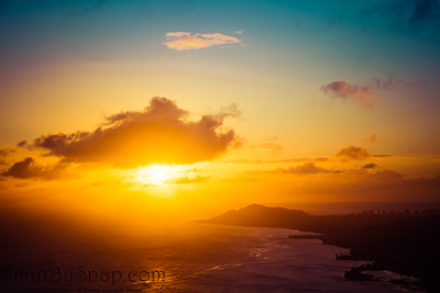 A sunset over the Hawaiian Island of Oahu as seen from a mountain top with the city of Waikiki Beach and Diamond Head in the distance.