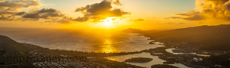 A panorama of a sunset over the Hawaiian Island of Oahu as seen from a mountain top with the city of Hawaii Kia in the foreground and Diamond Head in the distance.