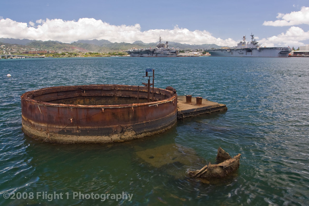 USS Arizona wreckage  in Pearl Harbor with modern aircraft carriers in the distance