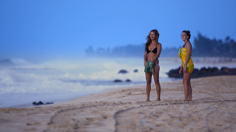 Two women pause on their stroll along the beach to watch the sun set.