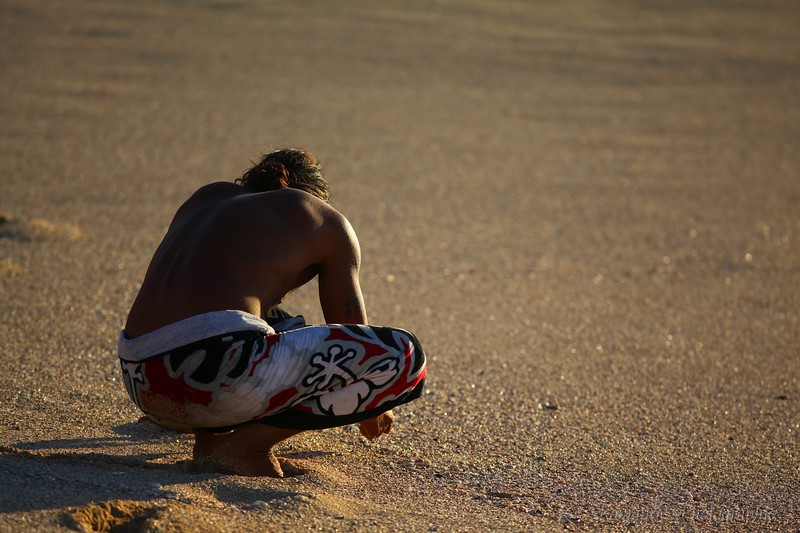 A native Hawaiian searches the sand for special shells.