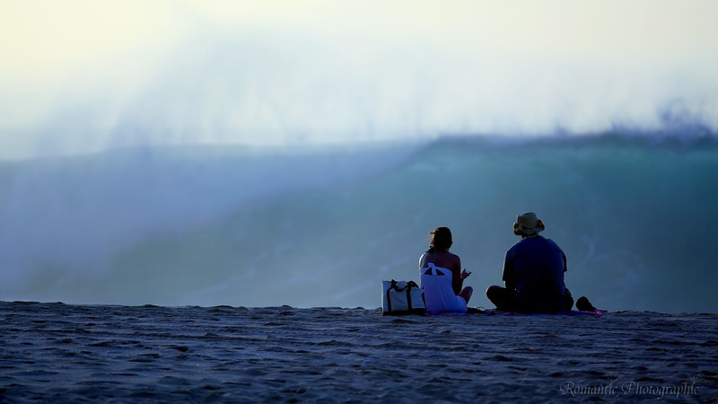 A couple enjoy watching the big surf roll in on the north shore.