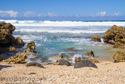 The clear blue waters of the Pacific Ocean splashing onto the rocky shoreline of