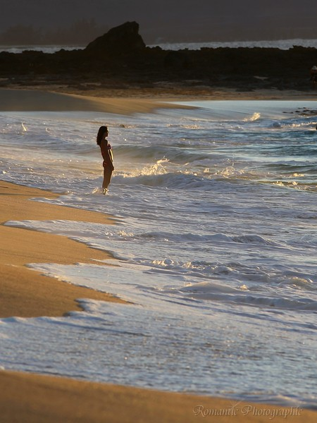 Awaiting the setting sun, a young woman stands at the surf's edge.