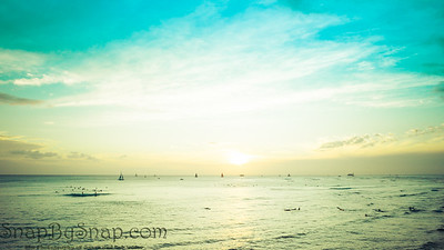 Surfers and sail boats in the ocean during sunset