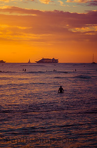 Surfer relaxing in the Pacific Ocean during sunset with a cruise ship on the horizon
