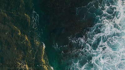 Ocean water from above with the left side of the image capturing the morning sunlight and the right covered in seafoam with the ocean floor visible in the center of the image