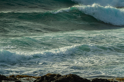 Rough blue ocean surf crashing into a rocky coastline