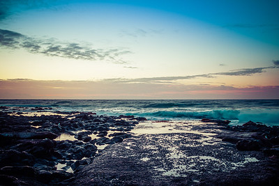Pre-dawn light over the ocean with a rocky foreground and rough surface crashing into the