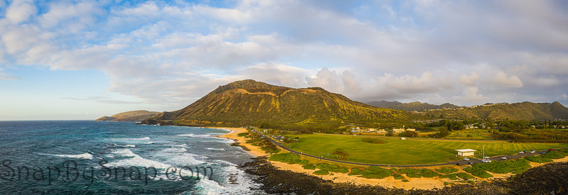 Panorama of Koko Head crater taken from a drone in Hawaii with both a rocky and a sandy beach with the incoming surf