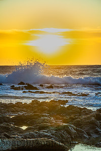 The sun rising over the ocean with a rocky foreground and rough surface crashing into the