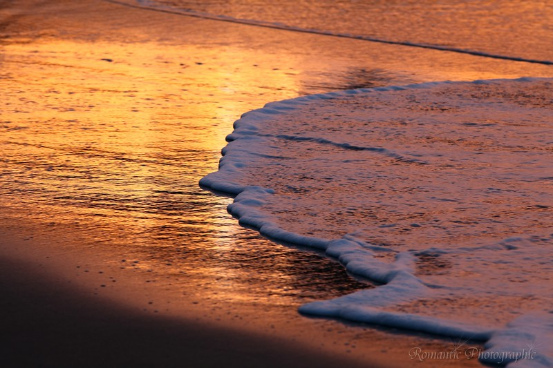 Surf boils over the golden sand.