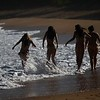 Girls dashing through the surf at Haena beach park.