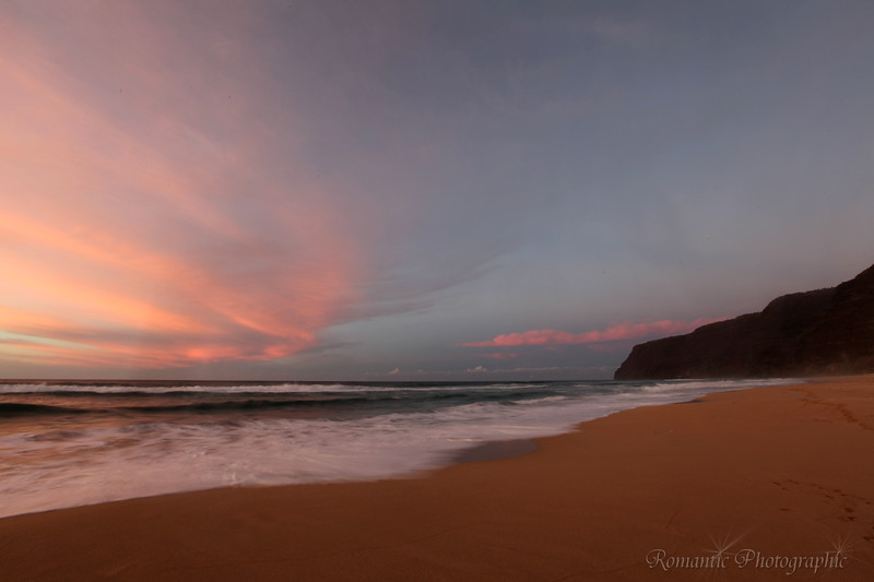 The setting sun leaves a red sky over the beach at Polihale State Park