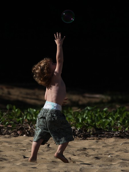A child on Haena beach park chases bubbles.