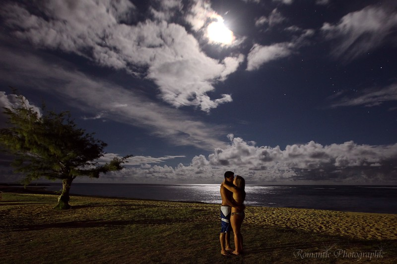 Braxten and Kayleigh pose under a moonlit beach on their honeymoon.