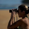 A woman on Haena Beach Park uses binoculars to watch her husband surf.