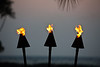 Tiki lamps lit at sunset on the grounds at the Fairmont Orchid, Brown's Beach House