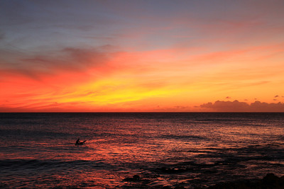 A surfer watches the sunset while waiting for one final wave of the day outside the Turtle Bay resort on Oahu's North Shore.
