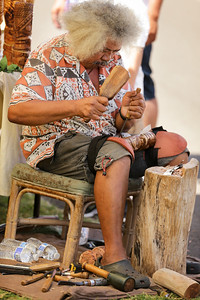 Man handcrafting a tiki at the Maui swap meet