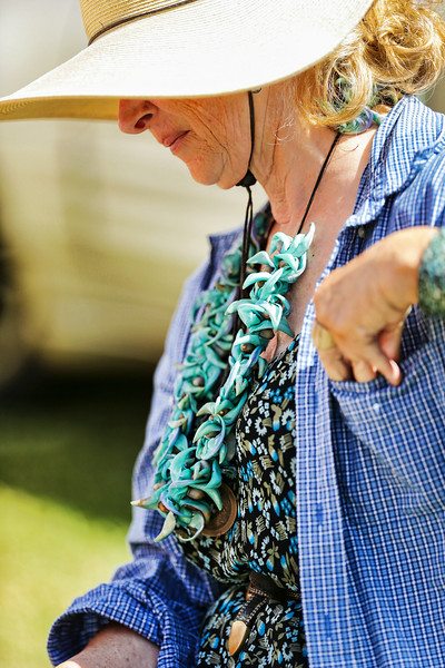 This vendor handcrafted this lei the morning of the swapmeet. The flower is a rare Jade Vine. I purchased it from her to photograph. The parking lot of the campus which holds the swap meet uses recycled glass chips around ornamental trees.