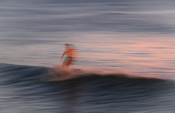 A surfer catches a late summer wave near the Turtle Bay resort on Oahu's North Shore.
