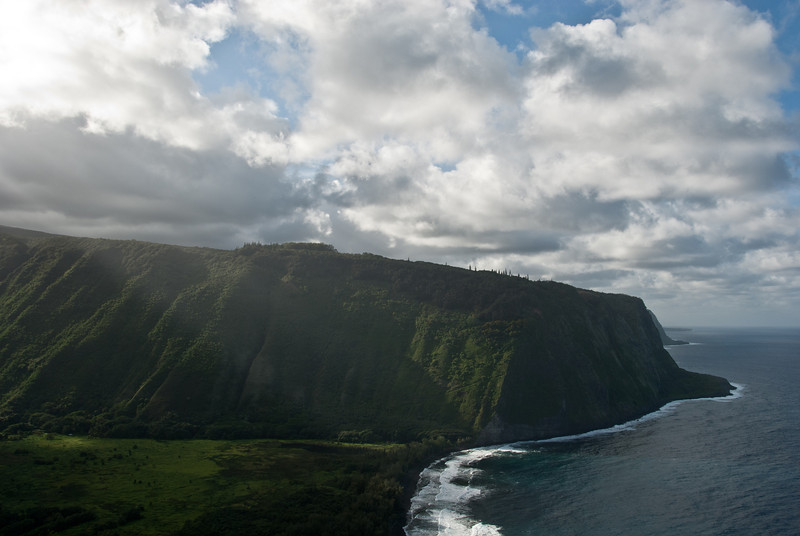 "<span id=""title"">Waipi'o Valley</span> <em>Waipi'o Valley, Hawaii</em> This valley is very sacred and we were urged to view it with respect and not enter it. Not that we could have if we tried - there are ominous signs everywhere about how you need a 4x4 to get anywhere - no AWD allowed. If you look at the map, this valley is the point where HI-19 cuts inland because the coast is far too rugged for a road. It was an impressive view, especially with the sunlight streaming through the clouds."