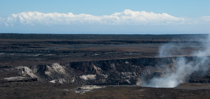 """<span id=""""title"""">Halema'uma'u Crater</span> <em>Hawaii Volcanoes National Park</em> I like the layers in this scene. In the foreground is the crater spewing sulfur dioxide from molten lava hundreds of feet below the ground, then the Kilauea caldera, then forest, then clouds."""