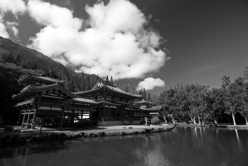 """<span id=""""title"""">Byodo-In Temple</span> <em>Byodo-In Temple, Kaneohe, Oahu</em> Built in 1968, it was established to commemorate the first Japanese immigrants and is a half-size scale replica of a 900 year old temple in Uji, Japan that has the same name. Not pictured is the separate Bell House (kanetsu-ki-do) that holds a 5 foot, 3 ton brass bell that we got to ring! As a fan of both soothing and bone rattling sounds, I was pleased to ring it (with a large, suspended piece of wood)."""