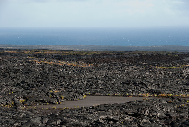 """<span id=""""title"""">Old Road</span> <em>Hawaii Volcanoes National Park</em> In the foreground you can see the old road where lava engulfed it. The landscape was really incredible here, just miles and miles of lava flows stopping at the ocean, as far as you can see. Almost no trees grow here, only small shrubby plants."""