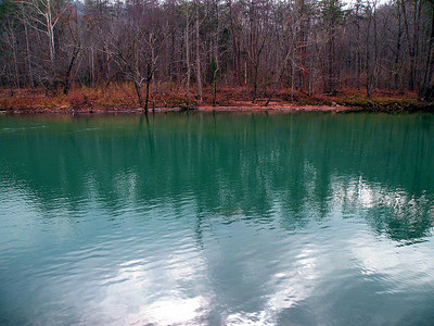 Blue green waters of the Caney Fork River.  It appears to be a normal river in Winter, but during Summer it's waters are absorbed by the limestone rock, disappear into subterranean caves and leave the river as a series of  holes of water.